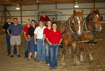 Morrie Waud joins the Morrie Waud Equine Center hospital staff in the facility's covered lameness exam arena.