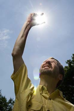 Photo of Jim Winkle holding his hand up to the sky as if to grasp the sun.