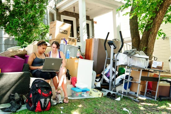 Photo of two students outside their apartment, surrounded by their belongings.