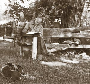 Aldo Leopold writing at the famous Shack with his dog Flick, 1940.