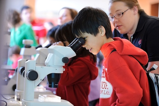 Photo: child looking into microscope