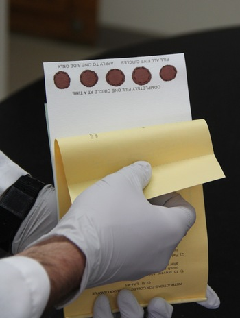 Photo: hands holding card with dried blood samples