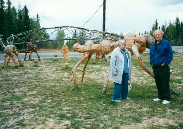 Photo: Gene and Lou DeFoliart in front of large bug sculpture