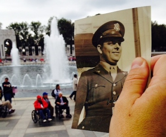 Photo: Mike Garren holding picture of father in uniform at WWII Memorial