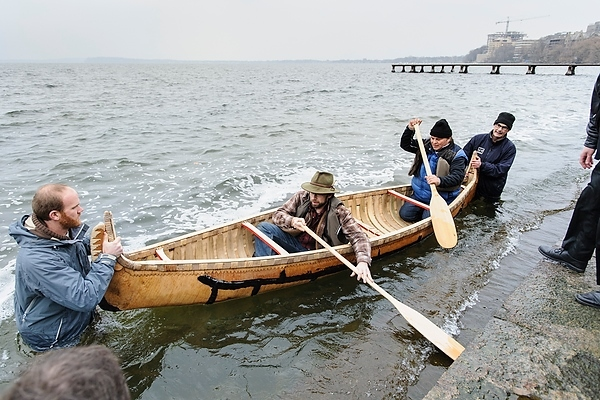 Photo: men launching canoe