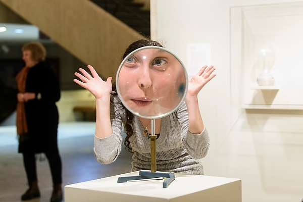 Photo: woman looking through large convex lens