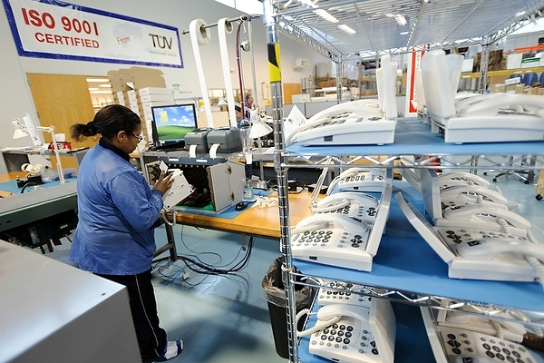 Photo: A worker programs and tests a new line of CapTel, a captioned telephone system, at one of Ultratec's multiple telecommunication and manufacturing facilities at the University Research Park
