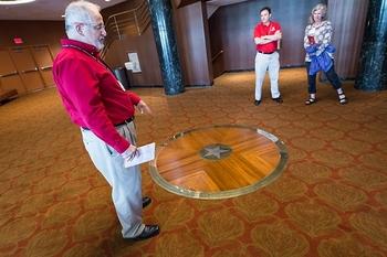 Photo: Ralph Russo gesturing toward commemorative star in floor