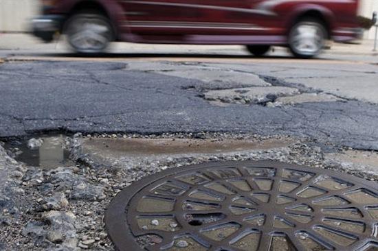 Photo: Crumbling asphalt in street around manhole cover