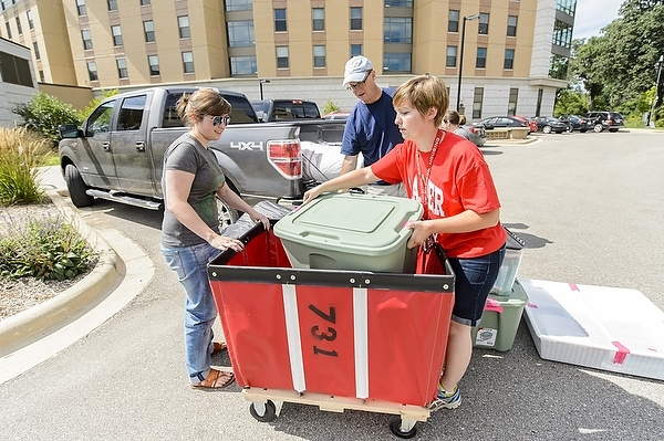 Photo: volunteer helping student move in to residence hall