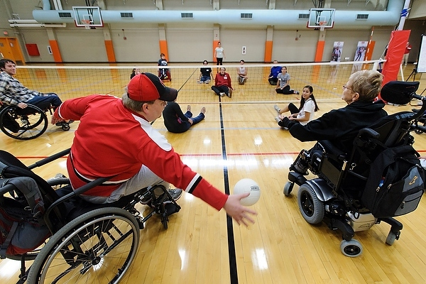 Photo: People playing sitting volleyball, some in wheelchairs