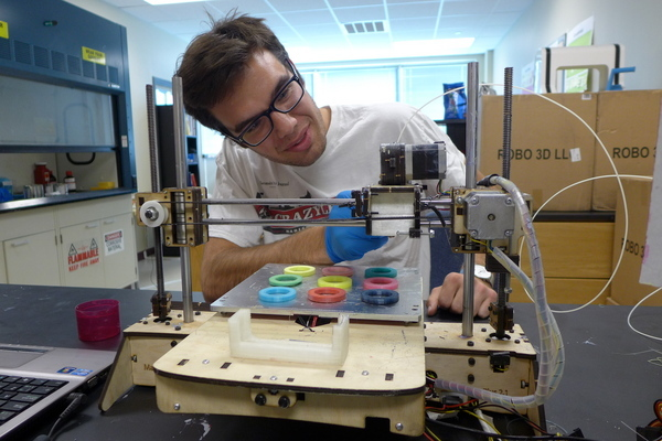 Photo: Chase Haider adjusts a commercial 3-D printer