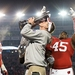 Photo: Coach Gary Andersen kisses the Big Ten West Division Trophy as Wisconsin players celebrate their team's victory