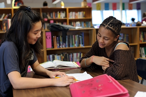 Sarah Soon, left, a University of Wisconsin–Madison undergraduate from Singapore and member of Badger Volunteers, reviews a math exercise with sixth grader Chaya Miller during an after-school tutoring program at Velma Hamilton Middle School in Madison, Wis. Badger Volunteers, initiated in Fall 2008 and coordinated by the UW–Madison Morgridge Center for Public Service, sends 70 student teams to 50 community-partner sites. More than 400 students participate each semester.